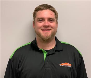 Male with light brown hair, black shirt with green trim and SERVPRO logo in front of a grn/gry wall